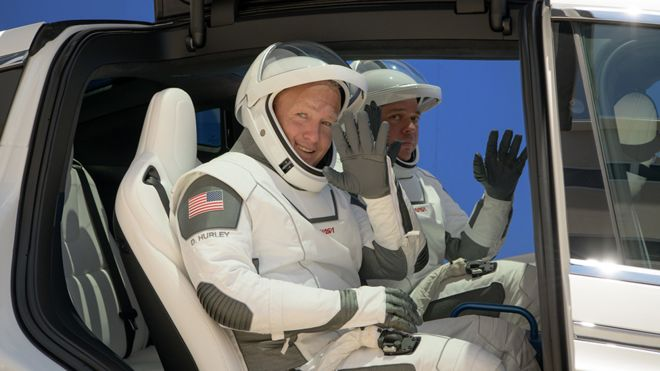 Astronauts drive to the starting ship in a Tesla vehicle.