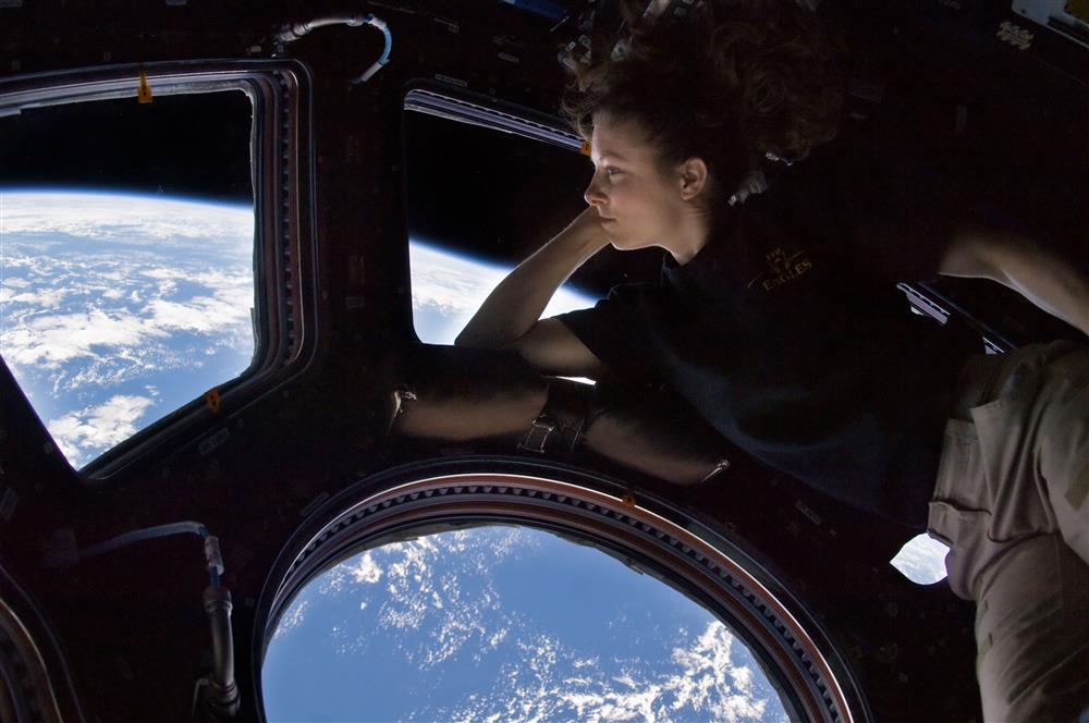 The astronaut observes the earth through a window on the dome of the International Space Station.